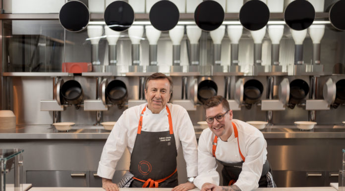 Cheffs-Daniel-Boulud-and-Sam-Benson of Spyce in front of their robotic kitchen