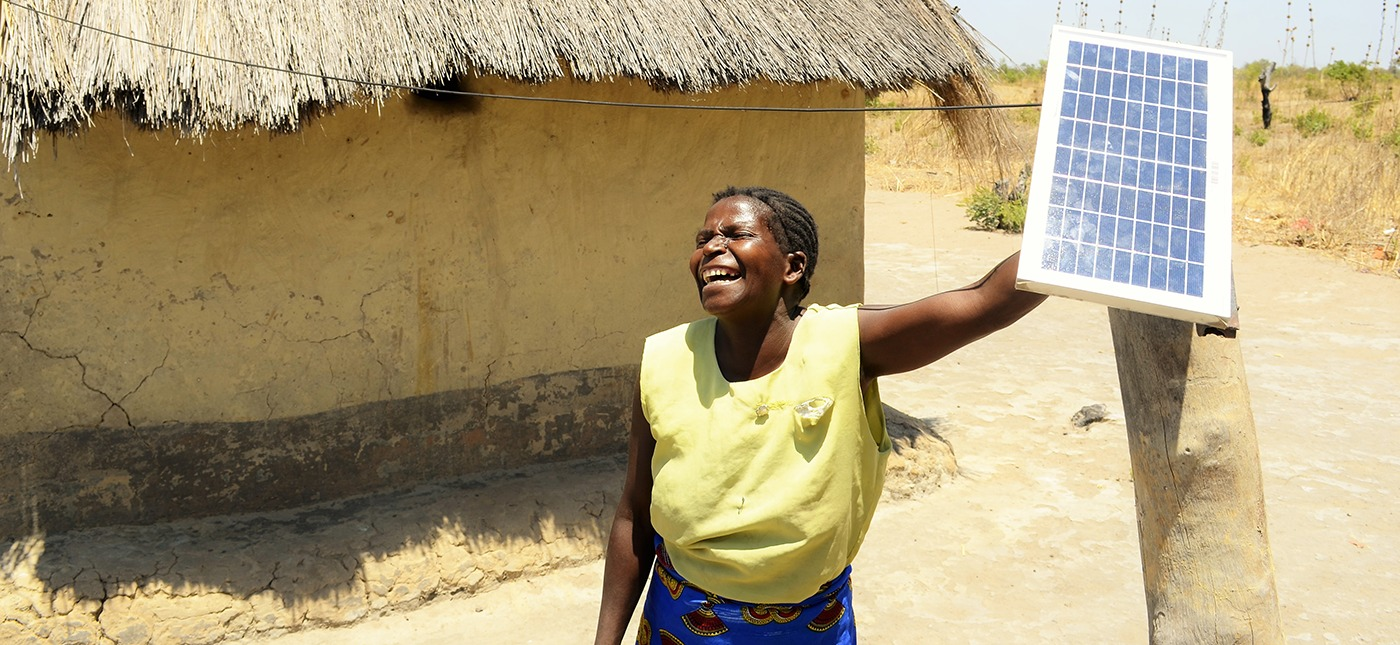 A woman from Africa is laughing and holding a solar panel crowdfunded thanks to Trine.