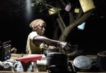 African women cleaning dishes in a dark room lit by a light source powered by solar energy.
