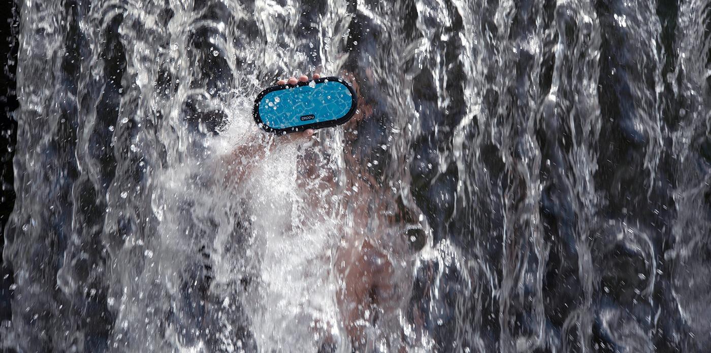 Man holding Zeppy blue wireless Bluetooth speaker under a waterfall.