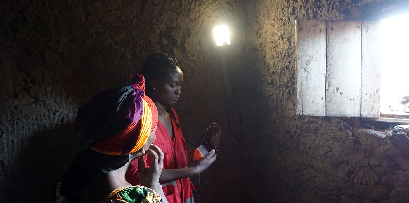 African woman in a dark room lit only by nowlight developed by startup Deciwatt