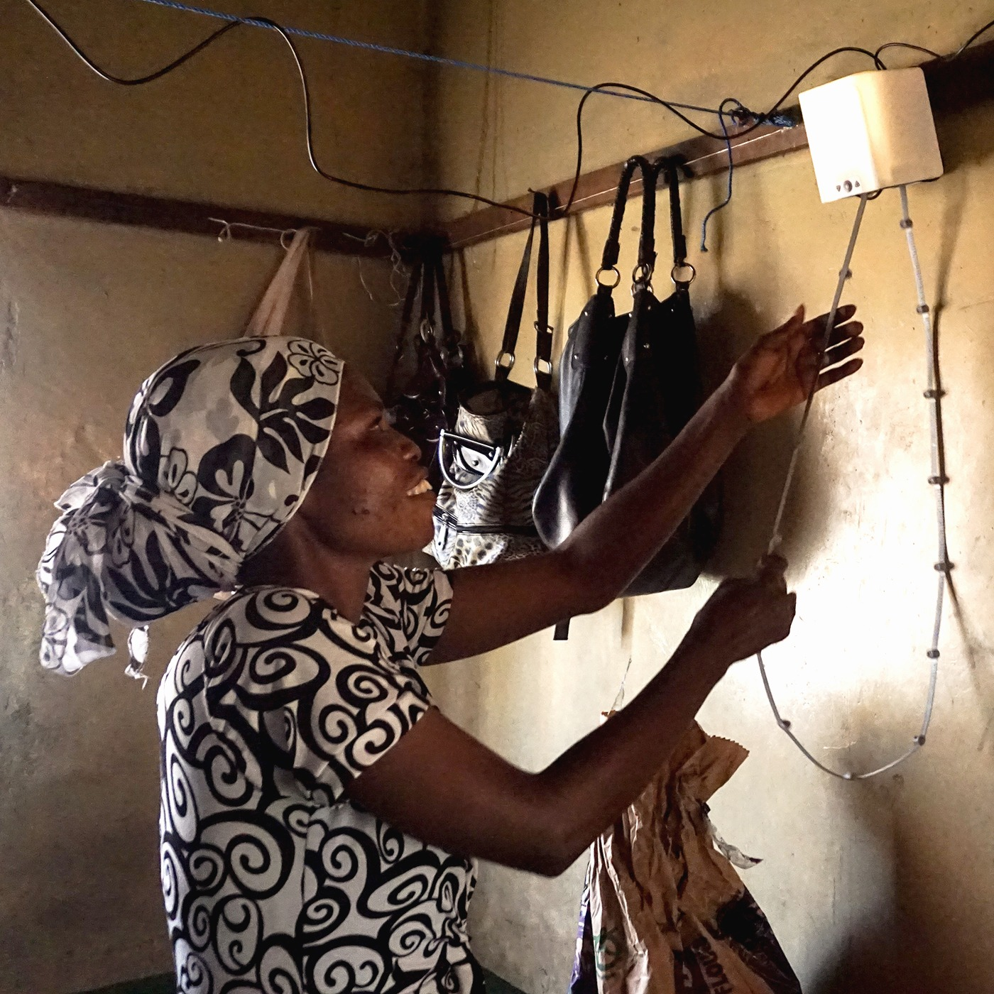 African woman pulling on a cord of nowlight – green off-grid light developed by startup Deciwatt.