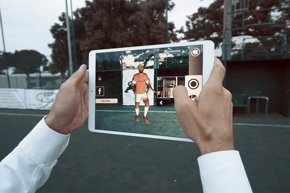 Man holding a tablet with AR Market app displaying a football player on a football field.
