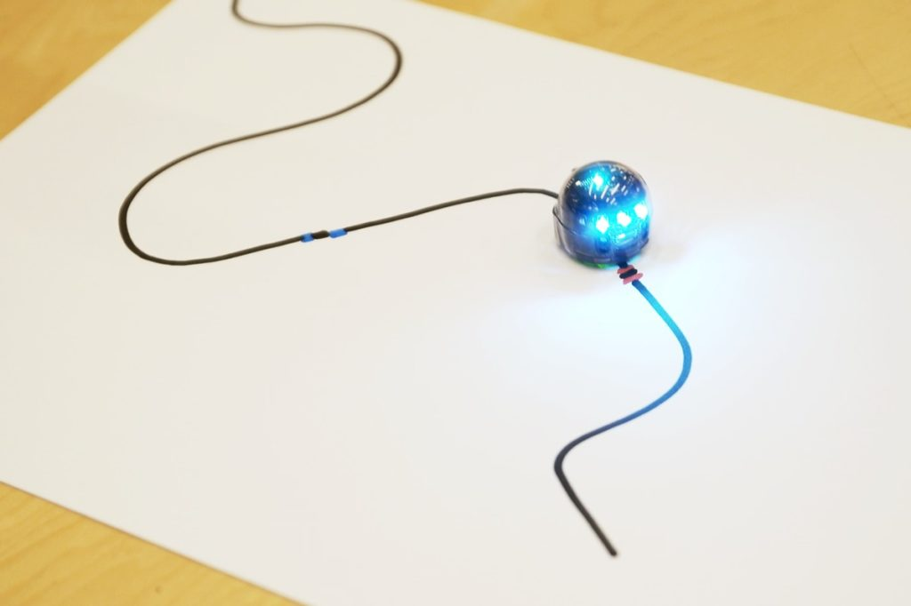 Little robot Ozobot following a path on a white sheet of paper drawn by a special black permanent marker.