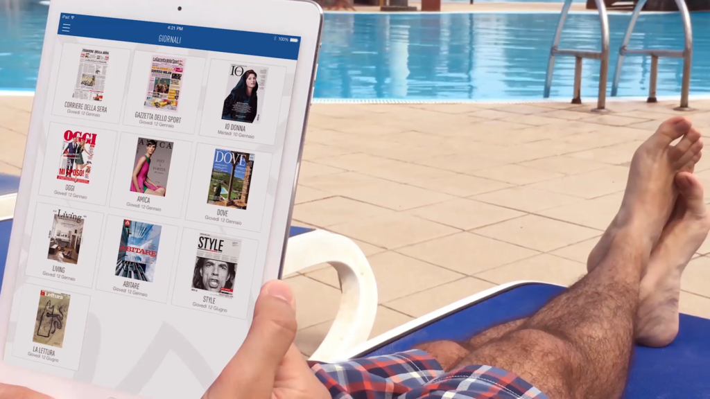 Man lying on a sun-bed and reading free digital content from Quibee.