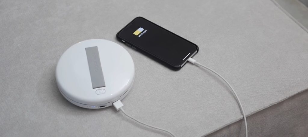 CleanseBot bacteria killing robot charging an iPhone lying on a bed.