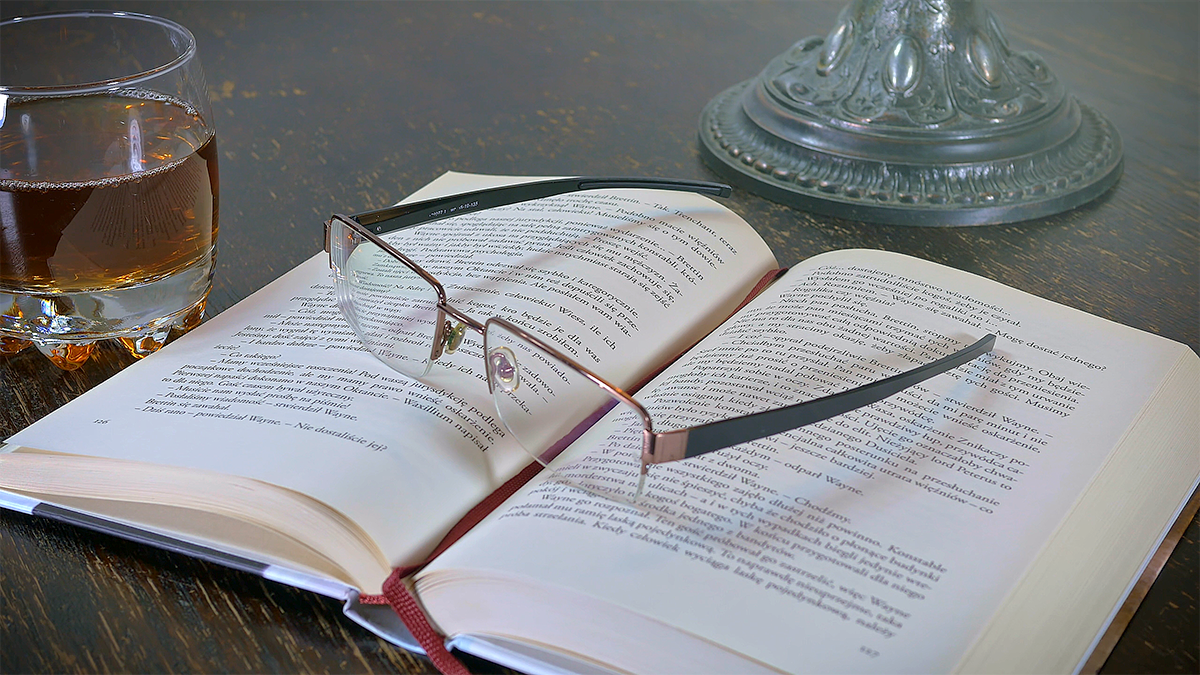 Polish book open on a table with glasses on top and a whisky glass in the background. Close up.