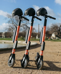 Three VOI electric scooters in a sand with helmets.