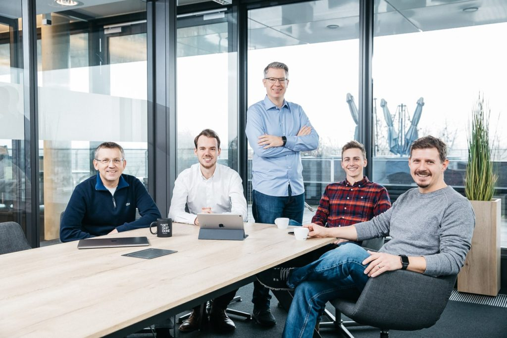 The Kraftblock team around a desk in their office.