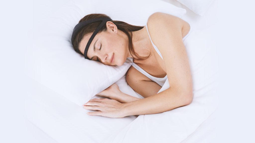 The Dreem Headband Gadget Being Worn by a Sleeping Woman.
